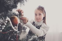 Pretty little girl decorate big christmas tree Royalty Free Stock Images