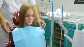 Pretty little girl in dental chair. Child dentistry. Dentist preparing little patient for treatment. Male dentist. Putting a napkin on young patient. Healthcare stock video footage