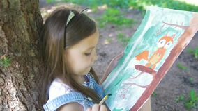 Pretty little girl drawing with gouache sitting near the tree in the park. Close up stock video footage