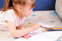 Pretty little girl draws picture Stock Photography