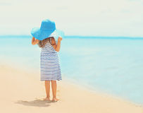 Pretty little girl in dress and straw hat enjoying sea Royalty Free Stock Photos
