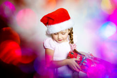 Pretty little girl dressed in santa red hat, new year portrait w Stock Image