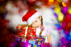 Pretty little girl dressed in santa red hat, new year portrait w Stock Photos