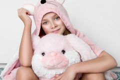 Pretty little girl wearing a warm sweater with rabbit ears sitting on the bed Stock Photo
