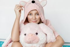 Pretty little girl wearing a warm sweater with rabbit ears sitting on the bed Stock Photos