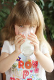 Pretty little girl is drinking milk Stock Images
