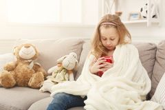 Beautiful little girl drinking tea at home. Pretty little girl drinking tea, sitting on sofa wrapped up in white knitted blanket. Cute pensive kid having pastime Royalty Free Stock Images