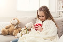 Beautiful little girl drinking tea at home. Pretty little girl drinking tea, sitting on sofa wrapped up in white knitted blanket. Cute pensive kid having pastime Stock Photo