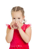 Pretty little girl drinking water from glass. Over white background Stock Images