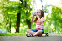 Pretty little girl drinking water while sitting on a skateboard outdoors Royalty Free Stock Photos