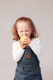 Pretty little girl eating apple in studio Royalty Free Stock Photo