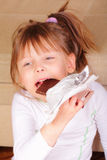 Pretty little girl eating chocolate Stock Photos