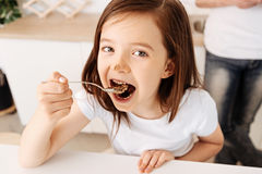Pretty little girl eating a chocolate cake. Enjoying dessert. Beautiful brown-haired girl enjoying a spoonful of cake and having some cream on her nose while her Stock Photo