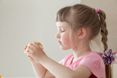Pretty little girl eating a doughnut Stock Photo