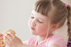 Pretty little girl eating a doughnut Stock Photos