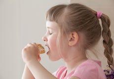 Pretty little girl eating a doughnut. With enjoyment stock photo
