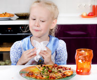 Pretty little girl eating homemade pizza Stock Images