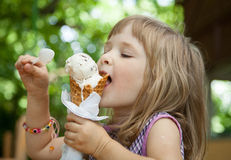 Pretty little girl eating an ice cream Stock Photos