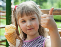 Pretty little girl eating an ice-cream. In a summer cafe Royalty Free Stock Photo
