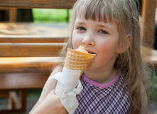 Pretty little girl eating an ice-cream. In a summer cafe Royalty Free Stock Photos