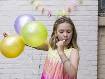 Pretty little girl eating a popsicle and holding balloons stock photos