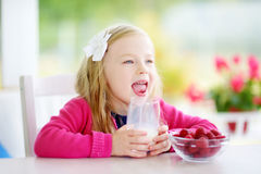 Pretty little girl eating raspberries and drinking milk at home. Cute child enjoying her healthy fresh fruits and berries. Stock Photos