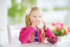 Pretty little girl eating raspberries and drinking milk at home. Cute child enjoying her healthy fresh fruits and berries. Royalty Free Stock Image