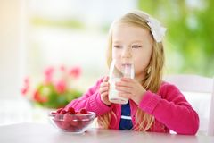 Pretty little girl eating raspberries and drinking milk at home. Cute child enjoying her healthy fresh organic fruits and berries. Stock Photos