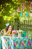 Pretty little girl eats strawberries and looks at camera at a table. Pretty little girl eats strawberries and looks at the camera at a table in the garden Stock Photography