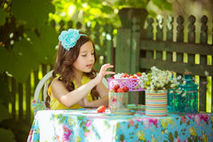 Pretty little girl eats strawberries at the table in garden. Pretty little girl eats strawberries at the table in the garden stock images