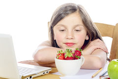 A pretty little girl eats strawberries Stock Images