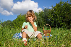 Pretty Little Girl eats sweet cherries in garden Royalty Free Stock Image