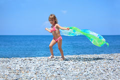Pretty little girl with fabric on stony seacoast Royalty Free Stock Photo