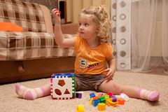 Pretty little girl on the floor with toy in hand Royalty Free Stock Photo