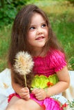 Pretty little girl with fluffy flower. Pretty little girl sitting on a beige cover with fluffy flower Royalty Free Stock Image