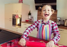 Pretty little girl with funny pigtails making christmas cookies Stock Image