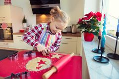 Pretty little girl with funny pigtails making christmas cookies Stock Photo