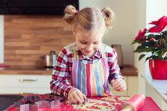 Pretty little girl with funny pigtails making christmas cookies Royalty Free Stock Image