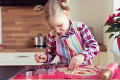 Pretty little girl with funny pigtails making christmas cookies Royalty Free Stock Photos