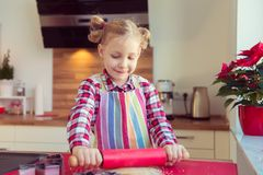 Pretty little girl with funny pigtails rolling dough for  christ Stock Photography