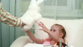 Pretty little girl getting white hare toy at her birthday table stock video