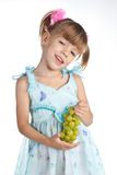 Pretty little girl with green grapes Stock Photos