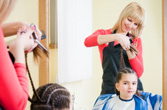 Pretty little girl in hairdresser salon Stock Photos