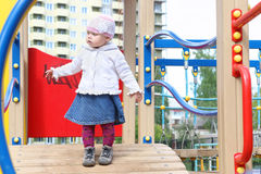 Pretty little girl in hat goes on bridge on playground Royalty Free Stock Images