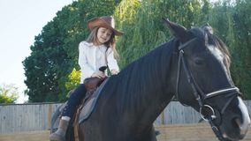 Pretty little girl in hat riding a black mare on the arena. 4K.  stock video