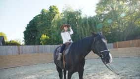 Pretty little girl in hat riding a black mare on the arena. 4K.  stock footage