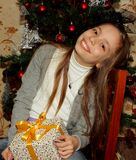 Pretty little girl in a hat sitting happy that she received a Christmas gift Stock Photo