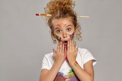Beautiful little girl with a painted fingers is posing on a gray background. Pretty little girl having a brush in her chic curly blond hair, wearing in a white stock photography