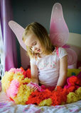 A pretty little girl on her bed in a fairy costume Royalty Free Stock Image