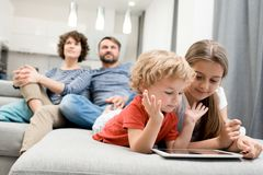 Usual Day of Lovely Family. Pretty little girl and her curly brother lying on cozy couch and playing game on digital tablet while their parents wrapped up in Royalty Free Stock Photos